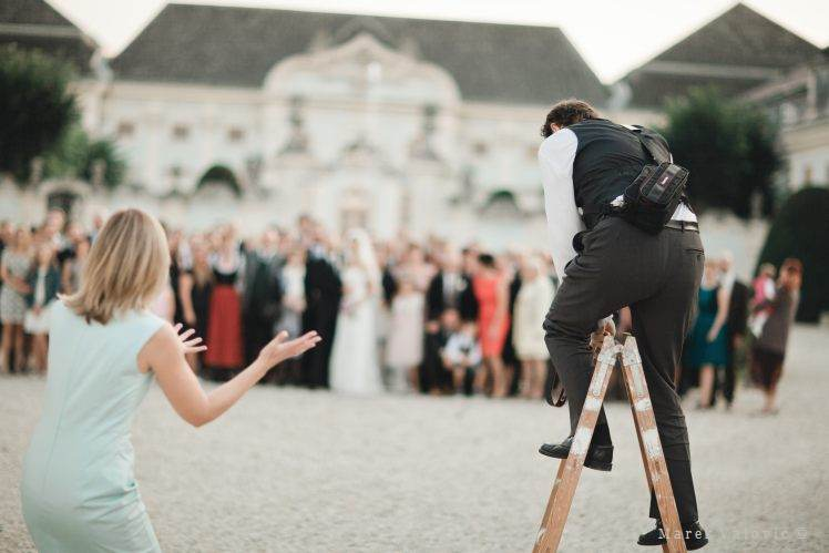 wedding photographer on a ladder to take group photo