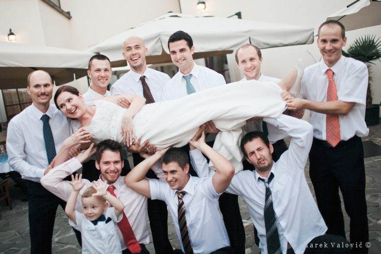 bride lifted on hands - group photo