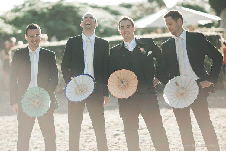 groom and bestmen having fun - group photo with parasoles