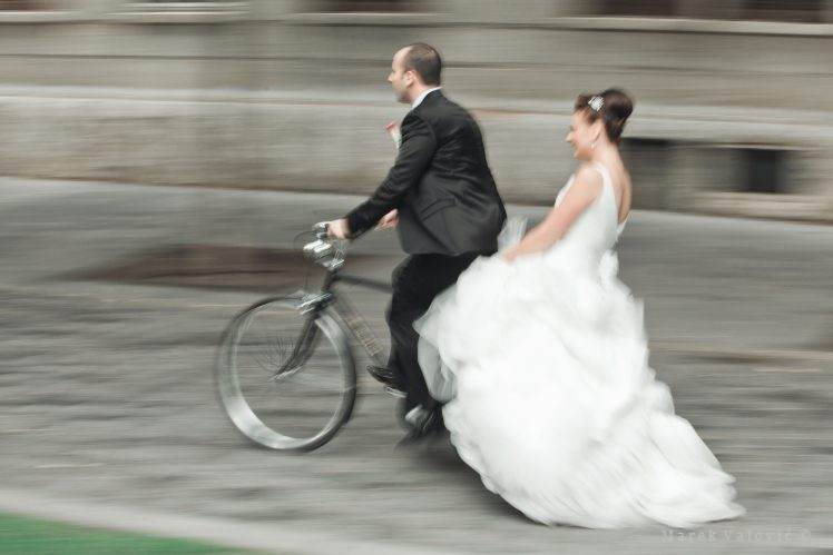 bride and groom on bicycle panning photo