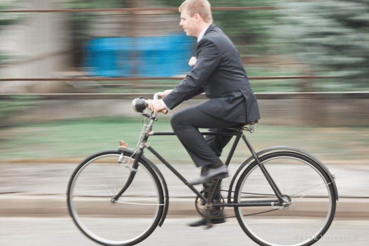 groom going on bicycle panning photo